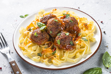 Meatballs in tomato sauce with pasta tagliatelle top view.