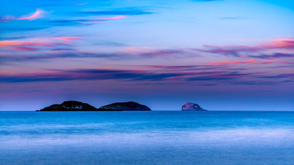 small island line up under clouds touch by the colour of last light at dusk