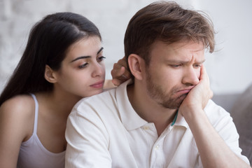 Loving young girlfriend comforting upset millennial boyfriend, showing support and care, female lover caress sad disappointed husband helping overcome troubles, asking for forgiveness or excuse