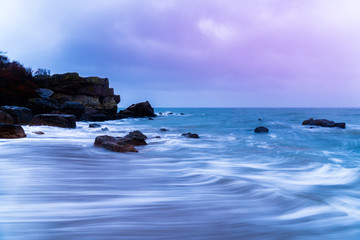 long exposure rocky beach with a purple sky