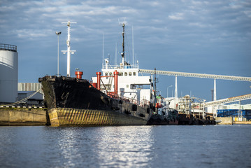 Close-up of the cargo ship in the port of Riga under a cloudy blue sky, Latvia