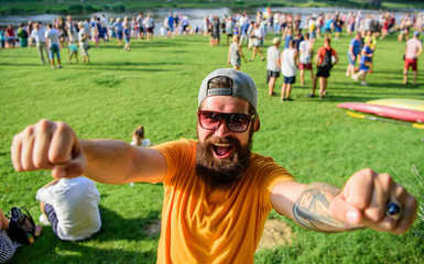 Urban event celebration. Cheerful fan at summer fest. Man bearded hipster in front of crowd people raise fists green riverside background. Hipster in cap happy celebrate event picnic fest or festival
