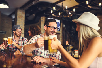 Young cheerful people in the beer pub drinking and having good time. Friendship concept with young people enjoying time together and having genuine fun at cool vintage pub