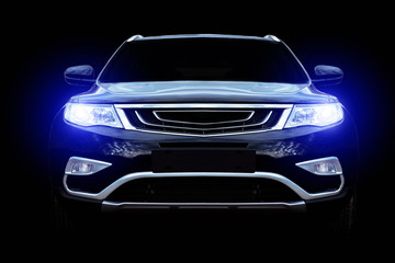 The car on a black background with shallow depth of field shines with headlights Wall mural
