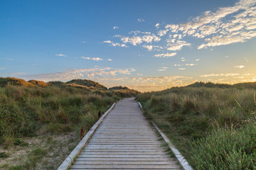 Foto op Canvas Donkergrijs A wooden pathway leading towards the sea at Formby in Merseyside, taken at sunset