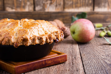 Apple pie in cast iron skillet on rustic wooden table