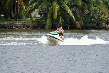 Recess Fitting Water Motor sports Happy young couple enjoying and having fun riding on a jet ski. Tropical coast of Sri Lanka