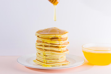 Pancakes on a white pink background. Hot pancakes with honey on a white plate. Delicious dish for breakfast. Honey flows down from a wooden stick on a dish. Homemade food
