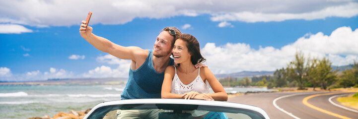 Wall Mural - car road trip vacation young people taking selfie photo with phone during summer travel vacation. Tourists couple taking photos on Hawaii in convertible car, with smartphone camera. Banner panorama.