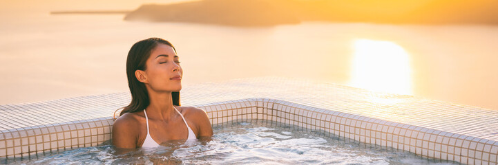 Luxury wellness spa jacuzzi pool Asian woman relaxing in swimming hot tub at outdoor hotel terrace. Banner panorama of young lady enjoying hydrotherapy massage water jets.
