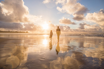 Father and daughter walking on an ocean beach during sunset