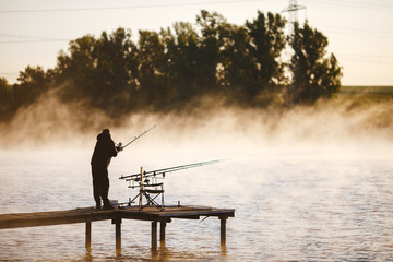 Fisher on the wooden pier to fish in the morning on sunrise. Pelt of feeder carp fishing rod