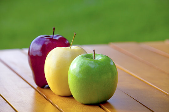 Three apples on a table red yellow and green