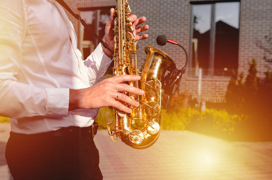 Golden Blues. Boys Band saxophone section at event , jazz player male playing on Saxophone, music instrument played by man saxophonist player musician at  folk classical . Alto sax hands Closeup