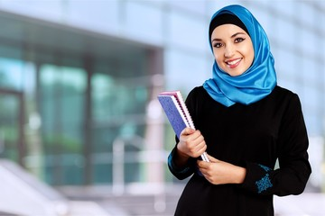 Happy saudi Arab student holding folders isolated on a white
