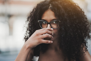 Close-up outdoor portrait of a charming young woman with long curly hair and in glasses drinking delicious coffee from a small glass cup, shallow depth of field
