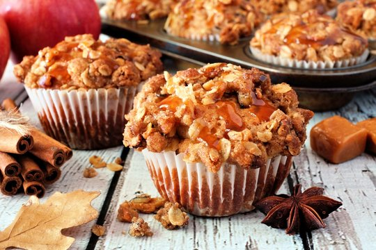 Autumn caramel apple muffins. Close up table scene on a white wood background.