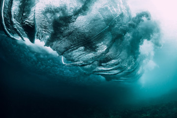 Barrel wave crashing in tropical ocean with sunlight. Underwater wave texture
