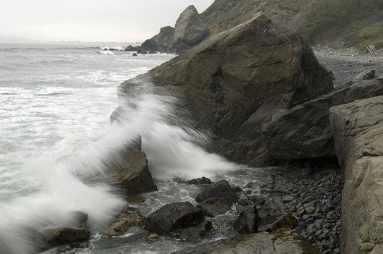 Waves crash along the rocky shoreline on Steep Ravine Beach in Mount Tamalpais, CA