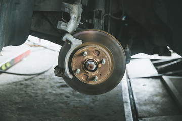 brake and detail of the wheel hub. car brake pads.disc brakes on cars in process of new tires replacement in the garage or auto repair service center, as background automotive concept.