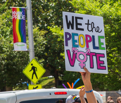 Voting sign being held up during the Pride Parade