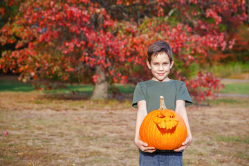 smiling boy and carved scary face on a pumpkin. portrait of a child with a Halloween pumpkin in his hands. Blurred background. copy space for your text