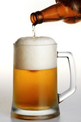 Bottle of beer being poured into a glass