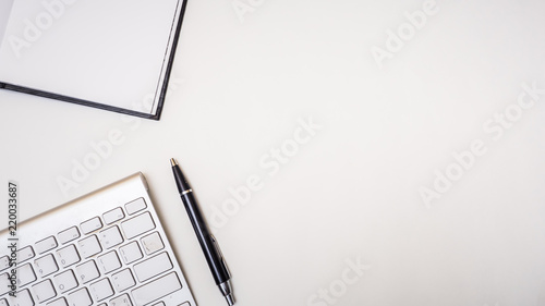 Wall mural Office desk table with notebook,keyboard and pen Top view on white background