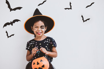 Happy asian little child girl in costumes and makeup having fun on Halloween celebration Fototapete