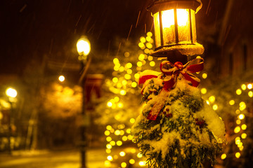 street lamp with Christmas decorations under the snow. White Christmas. spruce branches and a red bow on a lantern under a falling snow. Blurred background. Copy space for your text