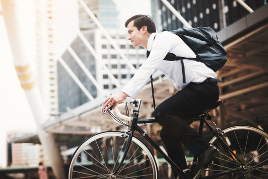 Handsome businessman caucasian wearing  white shirt with a necktie uniform in company employee using riding a bicycle work in the city, Concept healthy and ecology bike go to a work