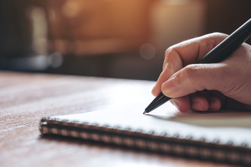 Closeup image of a hand writing down on a white blank notebook on wooden table