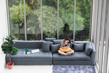 Asian woman sitting on the sofa near big glass windows, relaxing alone in house with green forest in background, taken from high angle. Wall mural