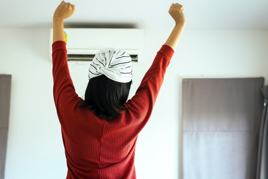 Happy fresh woman hands up and standing in front switching of the air conditioner