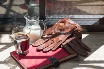Business of success book,milk jug,brown leather gloves and black coffee on wood near window in light morning.Copy space.