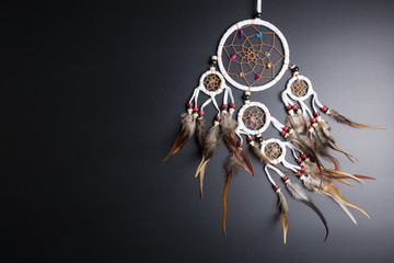Dream catcher with feathers threads and beads rope hanging spiritual folk american native indian amulet isolated on black background.Copy space for text.Concept prevent evil in Halloween.