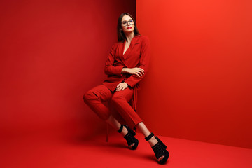 Fashion young woman in red suit. Wall mural