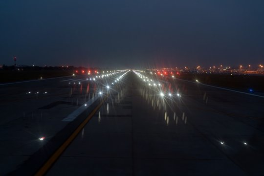 Landing lights ON A airport runway at night time.