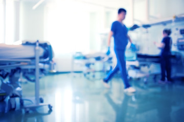 Working medical staff in the bright intensive care unit, unfocused background