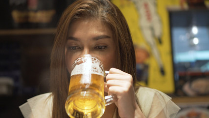 Beautiful asian woman drink beer in japanese restaurant