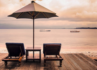 Two sunbeds and umbrella standing on a wooden platform on the tropical beach at sunset. Concept of calm rest