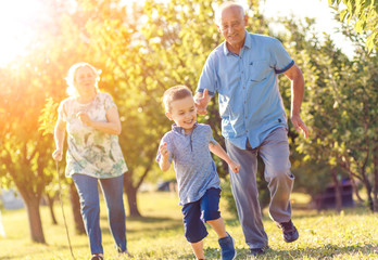 Grandparents with grandson enjoying time together in park.