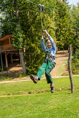 Smiling boy hanging from zip line