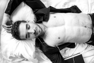 Concept of man with open shirt and abs lying in bed listening to audiobook