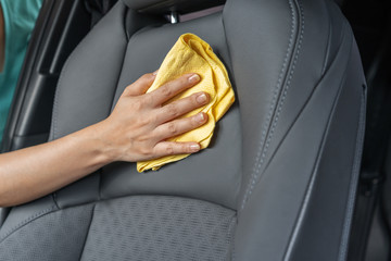 hand with microfiber cloth cleaning leather seat