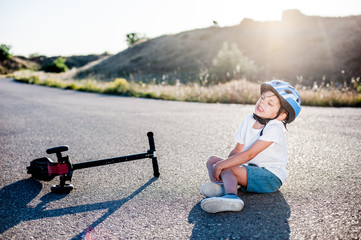 little kid in helmet sitting on asphalt road after accident with lying scooter