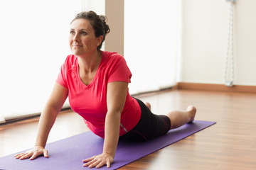 Smiling woman on purple mat doing upward facing dog yoga pose. Pretty female yogi practicing urdhva mukha svanasana in studio. Exercise, pilates, workout, sport outfit, healthy lifestyle concepts