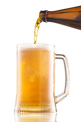 Pouring beer from bottle into a mug with foam isolated on white background.