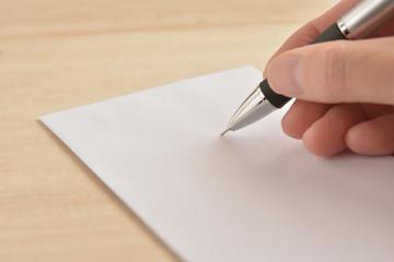 封筒 ペンを持つ手