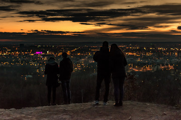couples lookin at a city from a mountain peak
